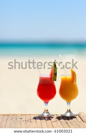 Vertical photo of two tropical fresh juices at tropical beach