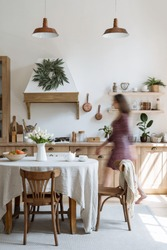 Vertical photo of woman walking in cozy house with modern kitchen interior. Female silhouette near contemporary furniture, dinner table, cooking hood, kitchenware supplies