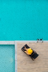 Vertical photo of Women relaxing and enjoying in the chair near luxury swimming pool. Copy space