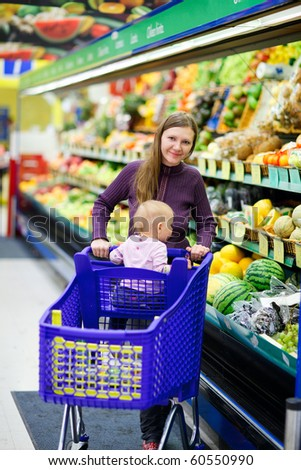 Vertical photo of young mother and her baby daughter shopping in supermarket