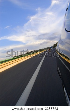 vertical picture of a car in movement in a highway, reflections in the car of the sky