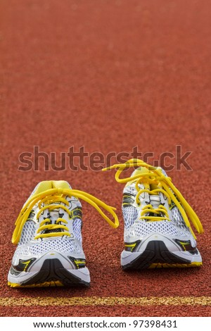 Vertical picture of a pair of runners on red tartan surface