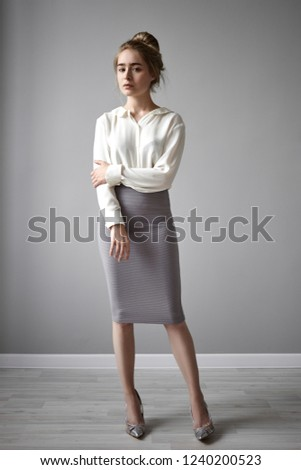 364ae2825f1d64 Vertical picture of gorgeous stylish young European lady in elegant white  blouse and tube skirt holding