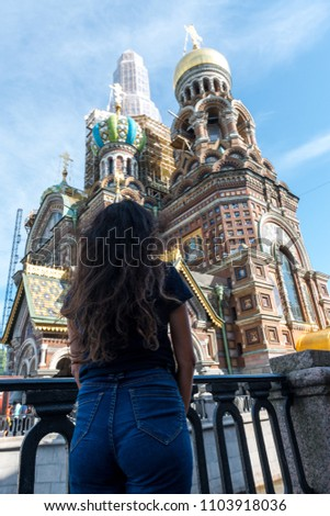 Vertical picture of the back of black hair woman looking to the Church of Our Savior on Spilled Blood (Church of the Resurrection of Jesus Christ), important landmark of Saint Petersburg, Russia.