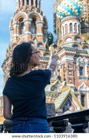 Vertical picture of the black hair woman looking to the Church of Our Savior on Spilled Blood (Church of the Resurrection of Jesus Christ), important landmark of Saint Petersburg, Russia.