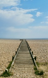 Vertical portrait image of wooden path or walkway leading across beach to sea