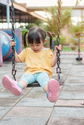 Vertical Portrait image of 2-3 years old baby. Happy Playful Asian child girl smiling and when she play the swing seat toy at the playground. Kids and development