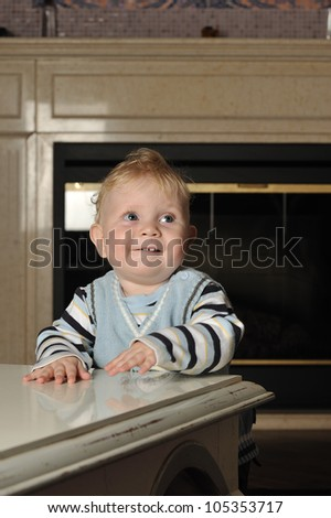 Vertical portrait of a baby boy in a striped sweater and a vest standing next to a coffee table looking up smiling