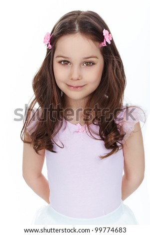 Vertical portrait of a charming girl smiling at camera, isolated on white background