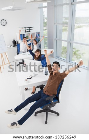 Vertical portrait of a cheerful business team with raised hands