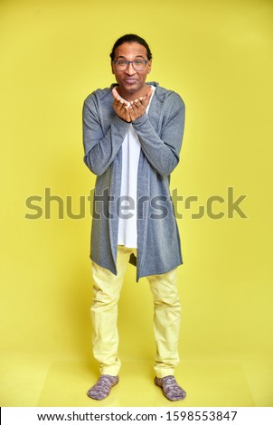 Vertical portrait of a cheerful young man wearing glasses African-American with a short haircut in ordinary clothes on a yellow background in full length. Standing right in front of the camera stock photo