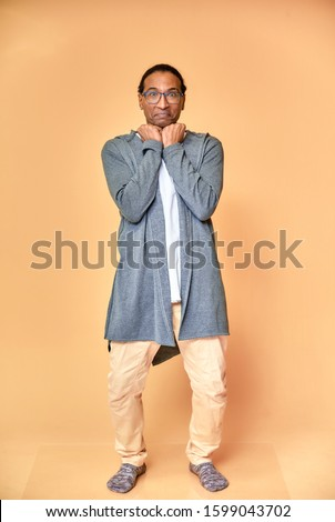 Vertical portrait of a cheerful young man wearing glasses African-American with a short haircut in ordinary clothes on a pink background in full length. Standing right in front of the camera stock photo