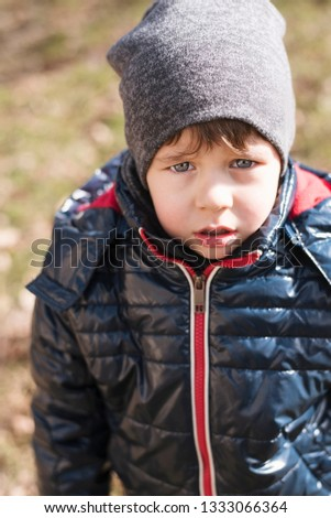 Vertical portrait of a sad little boy dressed in warm clothes and with a hat. The boy is sad because he can not wait for mom to walk with him. The boy lacks patience