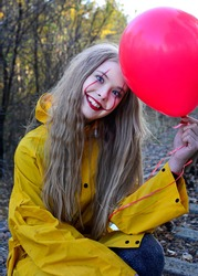 Vertical portrait of a smiling girl in a yellow raincoat with a clown make-up and a red ball in her hands. Halloween costume