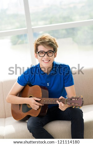 Vertical portrait of a smiling guy playing the guitar