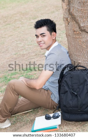 Vertical portrait of a student sitting near the tree outside