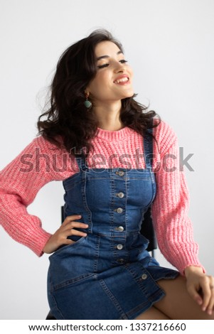 8345763e2d vertical portrait of a young cute armenian woman sitting on a chair and  posing