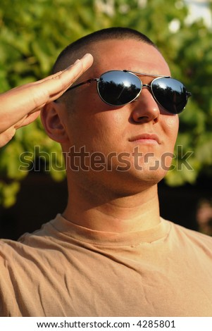 Vertical portrait of a young recruit in boot camp giving a salute