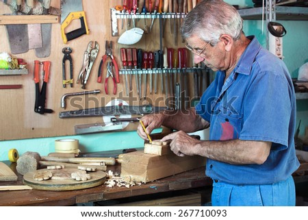 vertical portrait of carpenter marking with pencil handmade pieces of wood workshop / work cabinetmaker marking handcrafted wooden pieces in garage at home