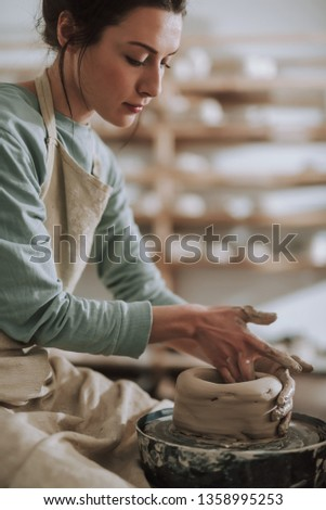 Vertical portrait of charming craftswoman making clay pot in pottery workshop