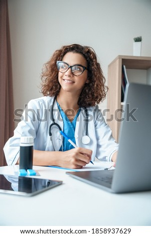 Vertical portrait of female doctor sitting on work desk and smiling. Telemedicine, Medical online, e health concept. Doctor using laptop for work, studying, video call and video chat with colleagues.