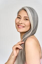 Vertical portrait of gorgeous happy joyful middle aged mature cheerful asian woman, senior older 50s gray haired lady isolated on white. Ads of aesthetic medicine spa salon hair care.