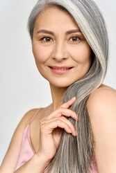 Vertical portrait of gorgeous happy joyful middle aged mature cheerful asian woman, senior older 50s gray haired lady isolated on white. Ads of hair care products for older salon haircare.