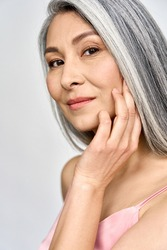 Vertical portrait of gorgeous happy middle aged mature asian woman, senior older 50 year lady looking at camera touching her face isolated on white. Ads of lifting anti wrinkle skin care, spa.