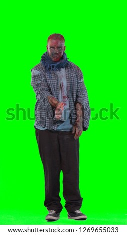 Vertical portrait of halloween theme horrible scary zombie, points at upper right corner with index finger, shows free space for your advertising content, isolated over green screen background