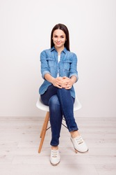 Vertical portrait of pretty young happy smiling lady in shirt and jeans sitting on a chair against white wall