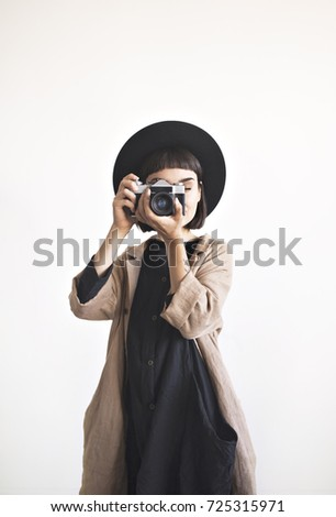 Vertical portrait of stylish young woman wears black dress, hat and beige linen coat. Girl takes pictures with her old film camera isolated on white wall background.