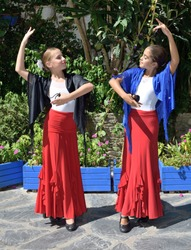 Vertical portrait of two girls dancing flamenco. They are in a symmetrical position with the typical handkerchief. It is a sunny day and a typical flamenco scene.
