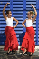 Vertical portrait of two girls dancing flamenco. They are in a symmetrical position with the typical handkerchief and looking at each other. It is a sunny day and a typical flamenco scene