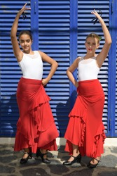 Vertical portrait of two girls dancing flamenco. They are in a symmetrical position with the typical handkerchief and looking at the camera. It is a sunny day and a typical flamenco scene