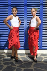Vertical portrait of two girls in a flamenco position. They are in a symmetrical position with the typical handkerchief and looking at the camera. It is a sunny day and a typical flamenco scene
