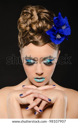 Vertical portrait of woman with blue make-up on dark background