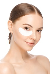Vertical portrait of young beautiful woman with glowing skin, wearing one eyepatch to eliminate puffiness, isolated on white background