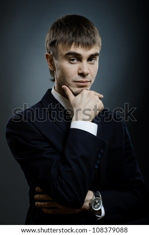 vertical portrait  the  young businessman  in costume , fixed look, on dark blue background