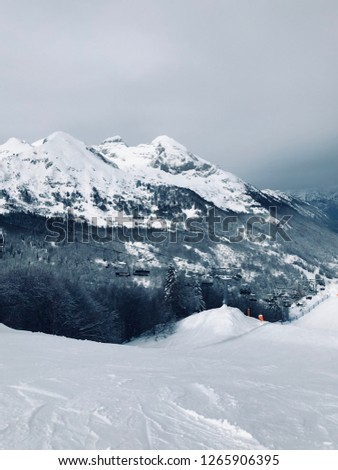 Vertical portrait view of a ski slope, ski lift, mountains and forest in Monte Cavallo (Piancavallo, Italy) in winter with snow and cloudy sky #1265906395