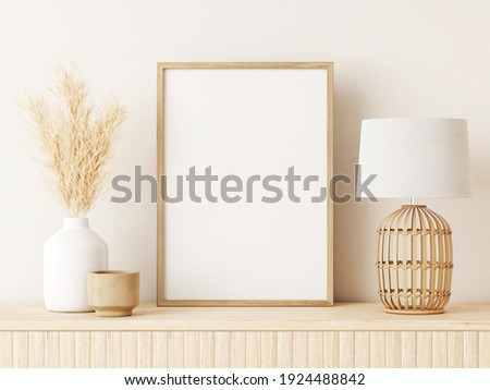 Vertical poster art mockup with beige wooden frame, dried grass in vase, wicker basket lamp on empty warm white background. Japandi interior decoration. A4, A3 format. 3d rendering, illustration