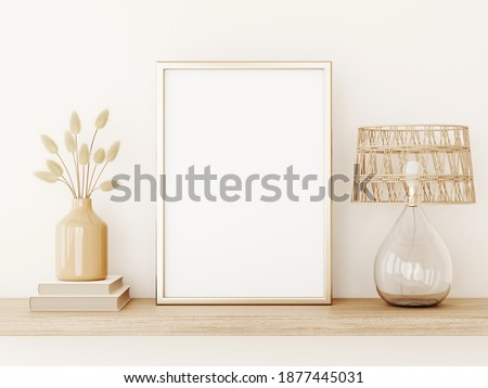 Vertical poster art mockup with gold metal frame, dried grass in vase, wicker lamp and books on empty warm beige wall background. Boho interior decoration. A4, A3 format. 3d rendering, illustration
