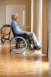 Vertical profile shot of a smiling senior man sitting in a wheelchair looking out of a door.
