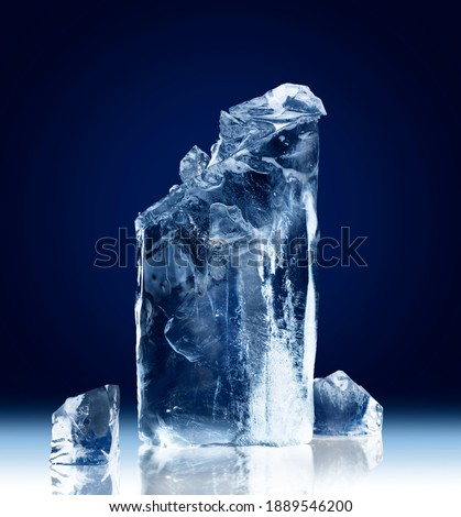 Vertical rectangular block of ice with a broken-off top isolated on a dark blue background with clipping path. Foto stock ©