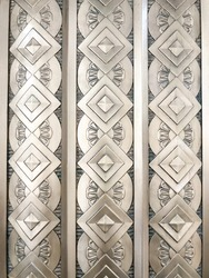 Vertical rows of repeating circle shapes, flower petals, and diamond-oriented squares decorate an exterior wall. The architectural style appears to be art deco, perhaps by casting or relief.