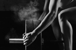 Vertical shot a female crossfit athlete preparing barbell for weightlifting at the gym magnesia protection powerlifting fitness strength athletics workout preparation focusng concentration, crossfit
