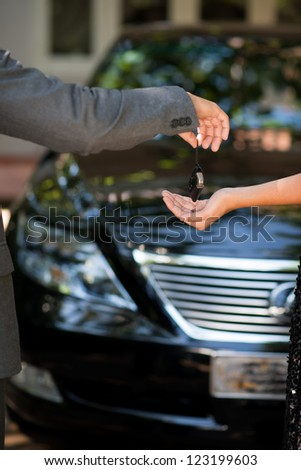 Vertical shot of a car dealer passing the key to the owner
