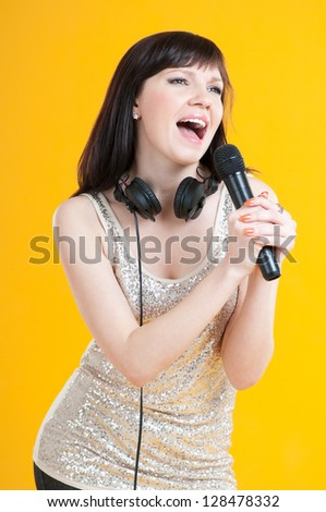 Vertical shot of a charming young woman singing with a microphone