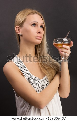 Vertical shot of a cheerful celebrating girl with a glass of drink