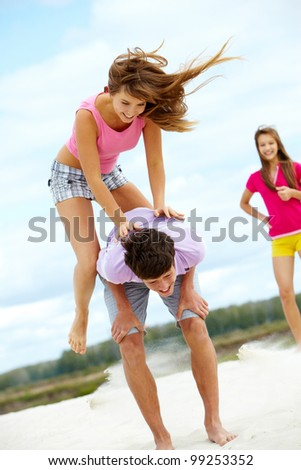 Vertical shot of a girl jumping over her friend�¢??s back, vivid an dynamic photo