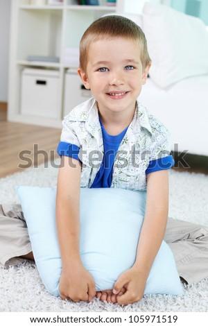 Vertical shot of a little guy hugging the pillow